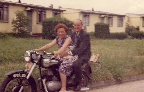 Martyn's grandparents on a motorbike outside the prefabs. Stapleford Road, Kings Norton