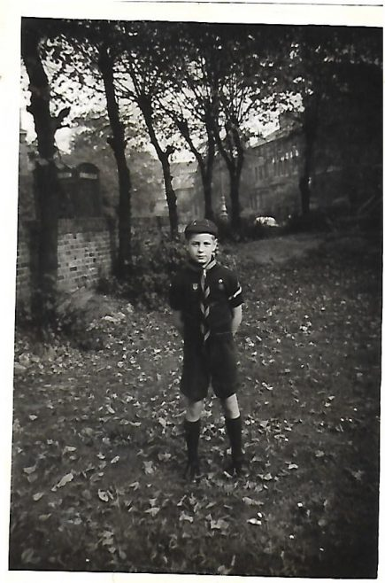 WOLF CUB JOHN BUGG IN GARDEN. MOUND BEHIND IS BURIED DEBRIS OF PREVIOUS BOMBED HOUSES. 1957