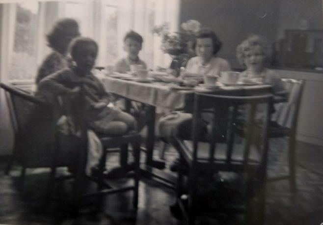 Family around the table. Swallow Street, Iver Heath, Buckinghamshire