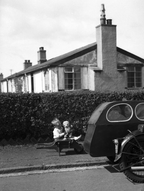 Child playing outside prefab in Dalmuir West, Clydebank