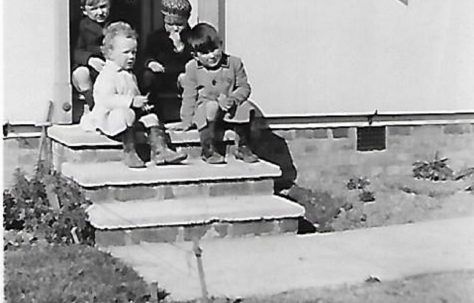 Pat (on the front at the right) and friends on the prefab steps, Douglas Road, Lenham