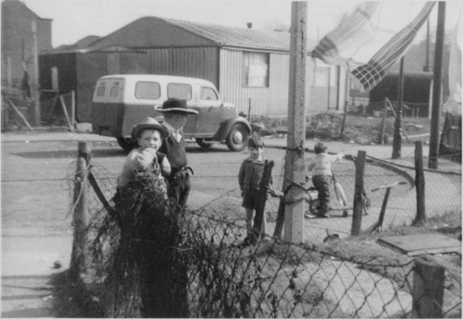 Nick Dowsett and Stephen Colwell playing cowboys in the banjo of Roding Avenue, Barking. No. 4 Roding Avenue is in the background | Nick Dowsett