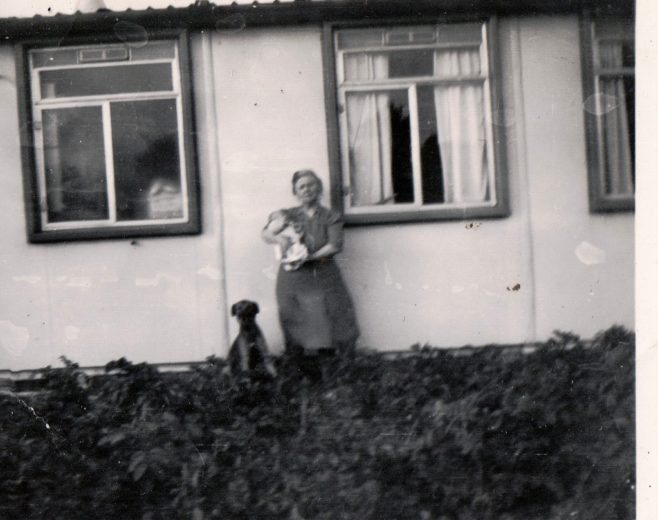 Winifred Arnold holding a baby (Roy Woollard) and a dog, plus dog sitting. 13 Mill Close, Ringmer | Kevin Arnold
